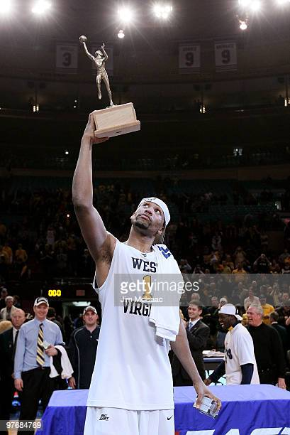 Da'Sean Butler of the West Virginia Mountaineers celebrates with the MVP trophy after defeating the Georgetown Hoyas in the championship of the 2010...