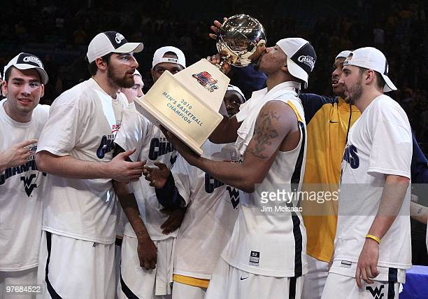 Da'Sean Butler of the West Virginia Mountaineers kisses the championship trophy after defeating the Georgetown Hoyas during the championship of the...