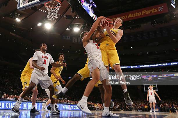 Dashawn McDowell of the Southern Methodist Mustangs fights for a rebound with Sean Lonergan of the Michigan Wolverines in the second half of the 2K...