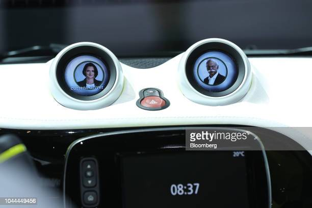 Dashboard driver information screens display the faces of Katrin Adt chief executive officer of Daimler AG's Smart brand left and Dieter Zetsche...