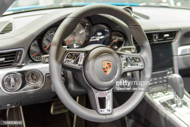 Dashboard on a Porsche 911 Cabriolet convertible sports car fitted with black leather seats and a large information display on the dashboard on...