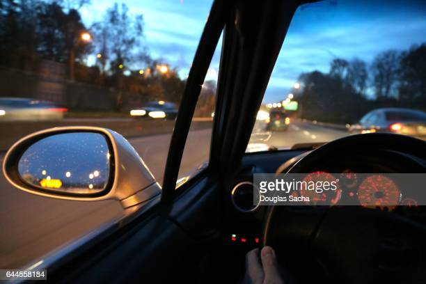 Dashboard view of a moving vehicle at dawn