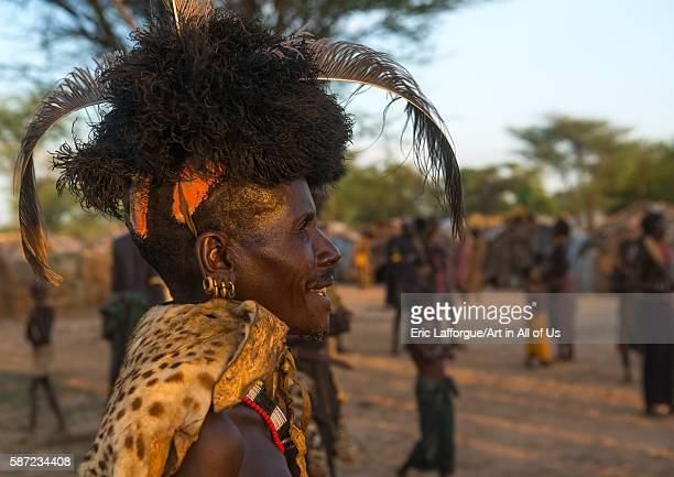 Dassanech man with leopard skin and ostrich feather headwears during dimi ceremony to celebrate circumcision of teenagers omo valley omorate Ethiopia...