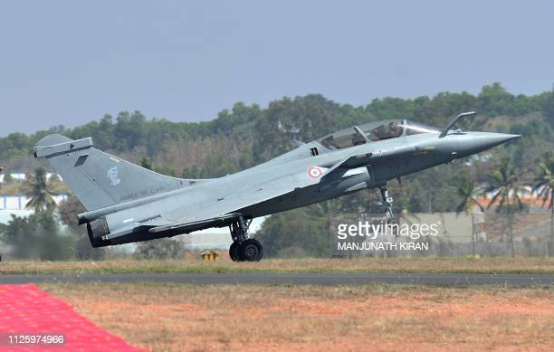 A Dassault's Rafale fighter jet lands after a flying display during the inaugural day of the fiveday Aero India 2019 airshow at the Yelahanka Air...