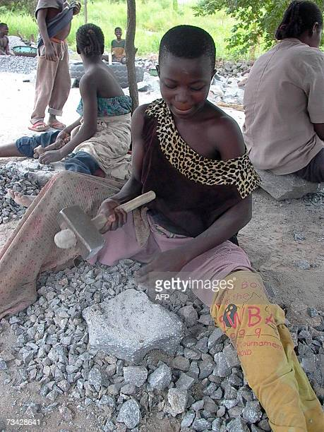 Thirteen yearold Gisele Badou pounds stones in a exacavation in DassaZoume some 200km north of Cotonou 25 February 2007 Gisele Badou had to leave...