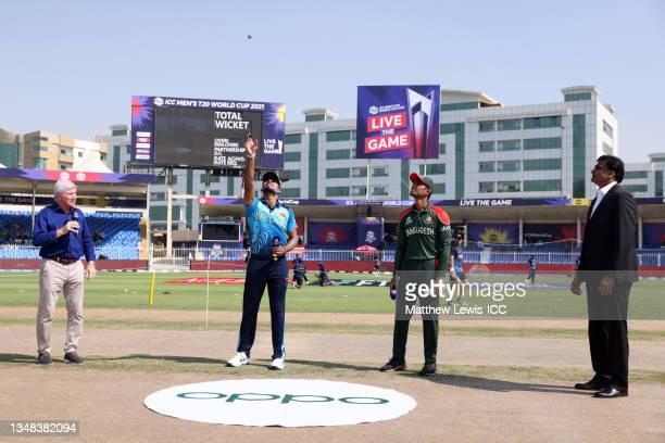 Dasun Shanaka of Sri Lanka flips the coin as Mahmudullah of Bangladesh looks on ahead of the ICC Men's T20 World Cup match between Sri Lanka and...