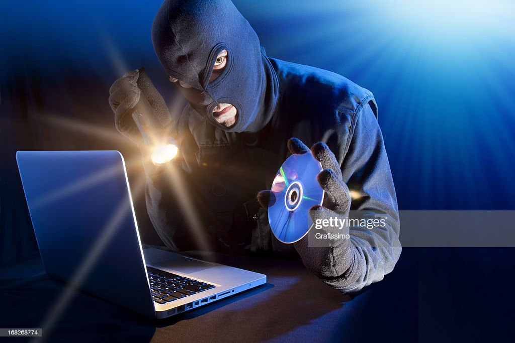 Data thief stealing DVD from laptop : Stock Photo