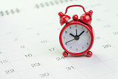Date and time reminder or deadline concept, small red alarm clock on white clean calendar with number of day, counting down to holiday, vacation or end of month