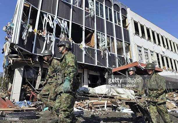 DATELINEJapanese soldiers carry on with rescue operations as they walk past a damaged building in the city of Rikuzentakata in Iwate prefecture on...
