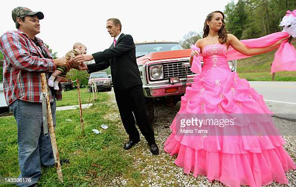 Dates Coty Shouse and Destiny Duff gather as Destiny's father Ronnie Duff passes a baby to be photographed while preparing for the Owsley County High...