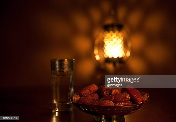 Dates with glass of water and illuminated lantern