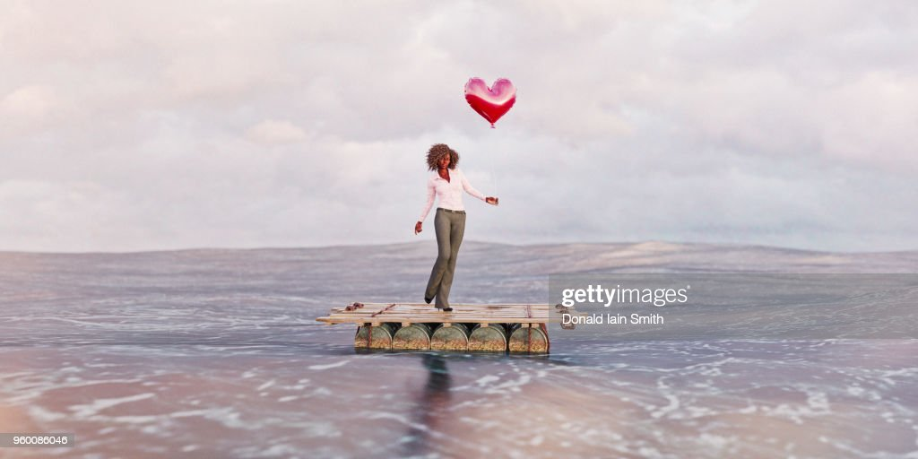 Dating concept: Woman on raft in ocean holding red heart shaped balloon : Stock-Foto