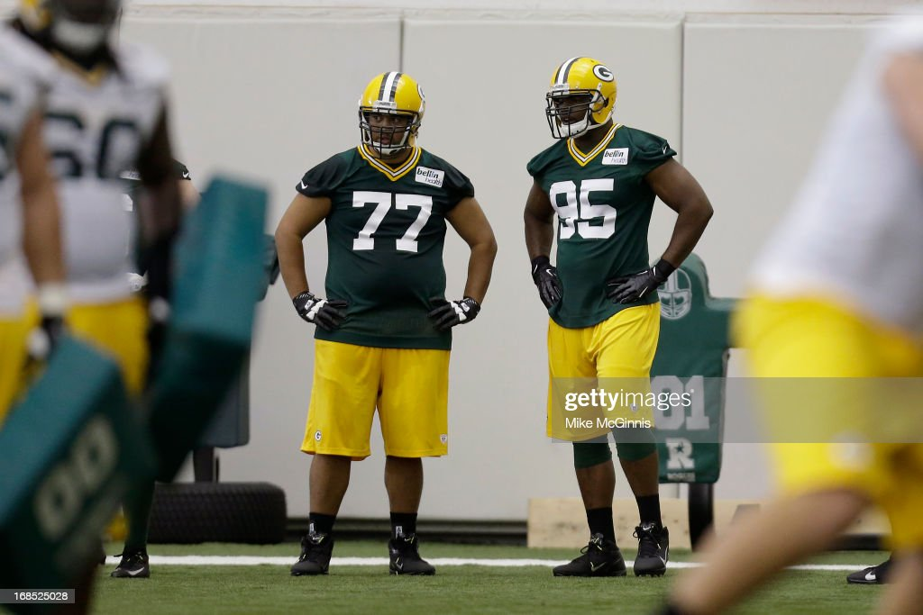 Datone Jones #95 of the Green Bay Packers and Castro Masaniai #77 watches the defensive line run through some drills during rookie camp at the Don Hutson Center on May 10, 2013 in Green Bay, Wisconsin.