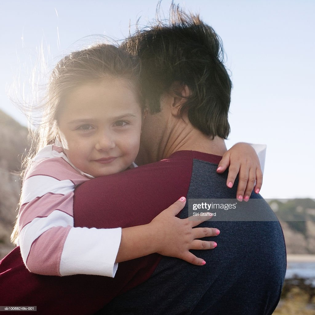 Daughter (6-7) and father hugging, girl looking at camera, outdoors : Stock Photo