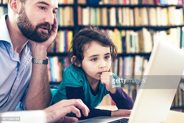 daughter and father looking concentrated at laptop