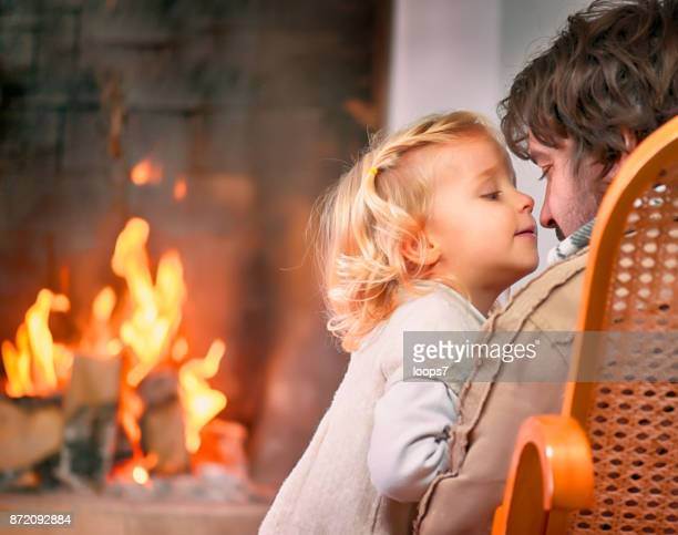 daughter and father near the fireplace - loops7 stock photos and pictures