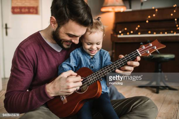 daughter and father playing guitars - plucking an instrument stock pictures, royalty-free photos & images
