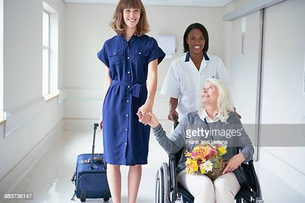 Daughter and hospital orderly pushing senior female patient in wheelchair