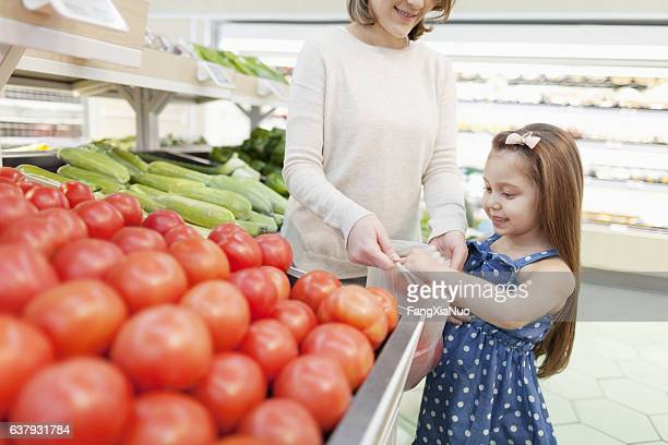 Daughter and mother shopping for produce in grocery store