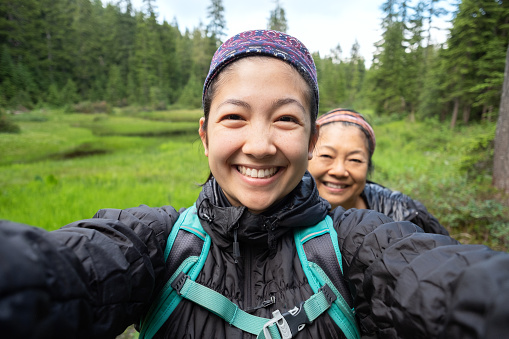 Daughter and Mother Taking Selfie While Hiking Along Alpine Lake 1161537856