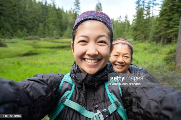 Daughter and Mother Taking Selfie While Hiking Along Alpine Lake