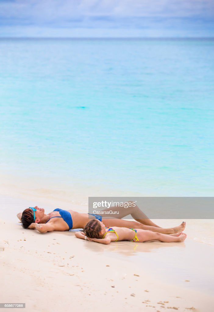 Daughter And Mother Taking Sunbath On Tropical Beach : Stock Photo