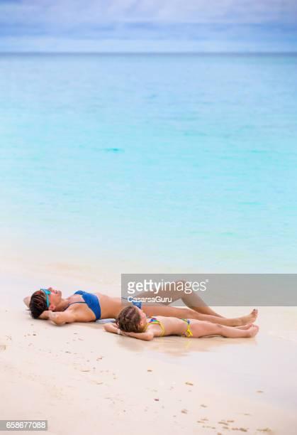 dochter en moeder nemen zonnen op tropisch strand - lagune stockfoto's en -beelden