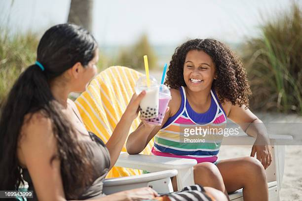 Daughter And Mother Toasting Boba Milk At Beach