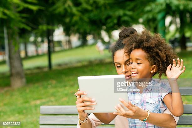 Daughter and mother using digital tablet at the park