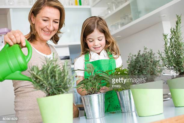 Daughter and mother watering herbs