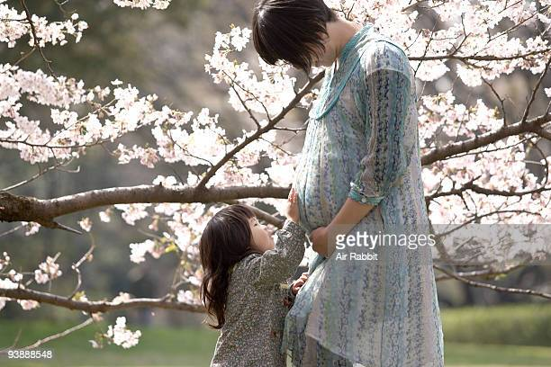 Daughter and pregnant woman under cherry blossoms