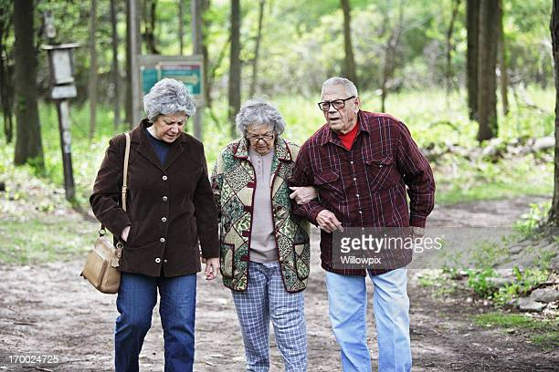 Daughter And Senior Parents Walking Together on Nature Trail