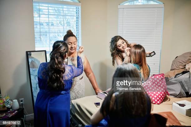 Daughter applying makeup on mother in bedroom before granddaughters quinceanera