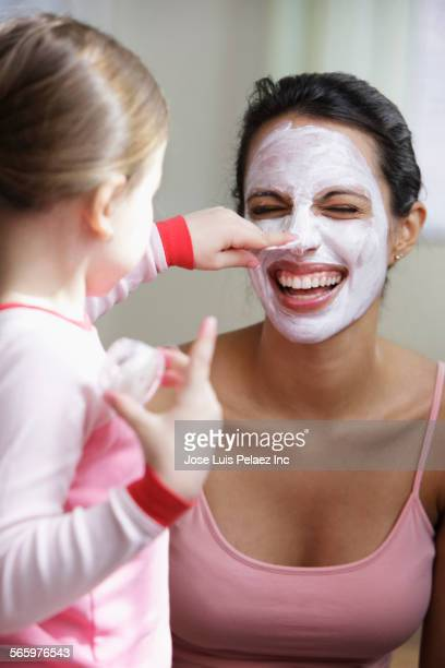 Daughter applying moisturizer to face of laughing mother