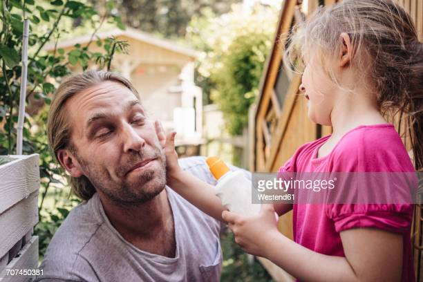 Daughter applying sunscreen on fathers face in garden