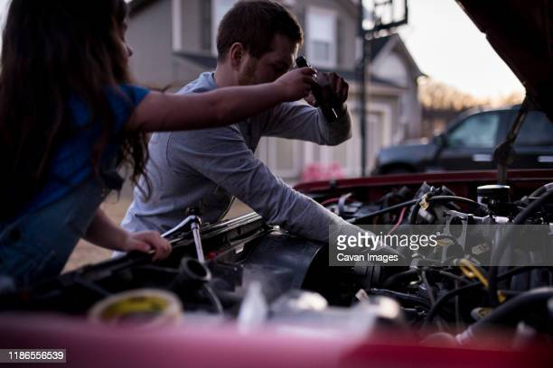 daughter assisting father in repairing car - adjusting stock pictures, royalty-free photos & images
