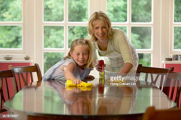 A Daughter Assisting her Mother Polish a Wooden Table in a Dining Room