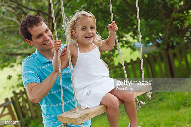 daughter being pushed on tree swing by father