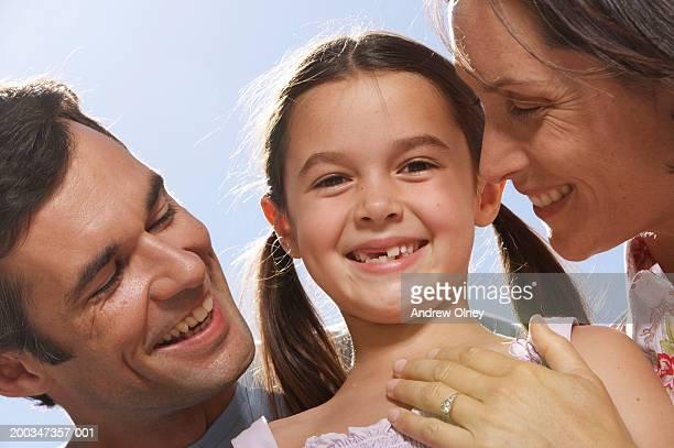 Daughter (5-7) between parents outdoors, smiling, portrait