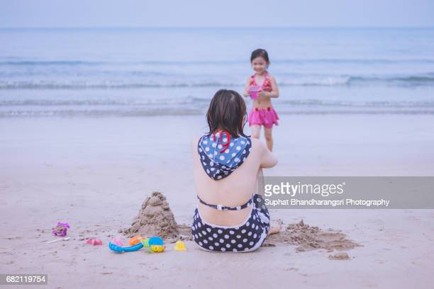 Daughter bringing more sand for her mother