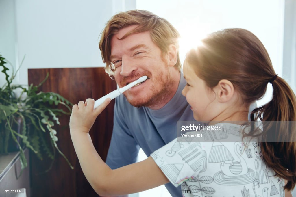 Daughter brushing her father's teeth in bathroom : Stock-Foto