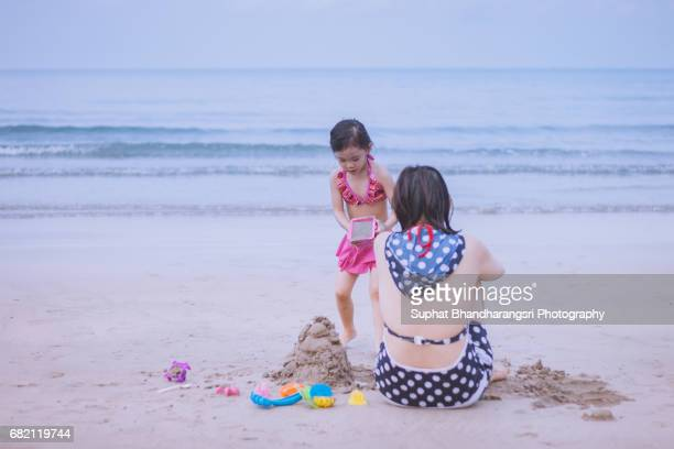 Daughter building sand castle with her mother