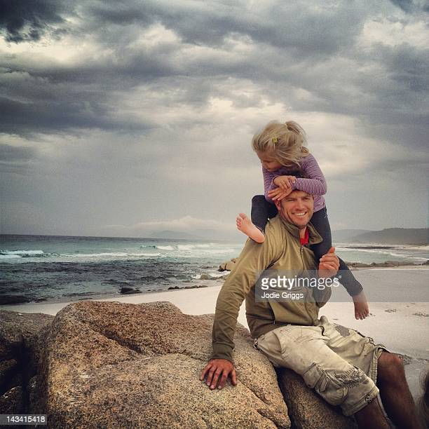 Daughter climbing on fathers shoulders at beach
