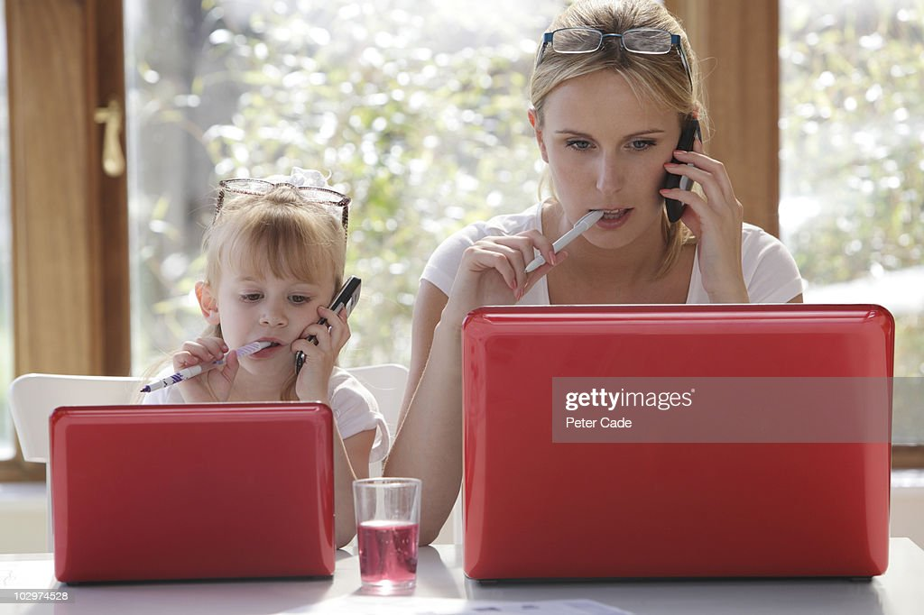 daughter copy mother working on laptop : Stock Photo