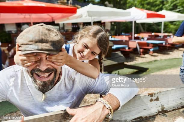daughter covering father's eyes on a playground - familie mit einem kind stock-fotos und bilder