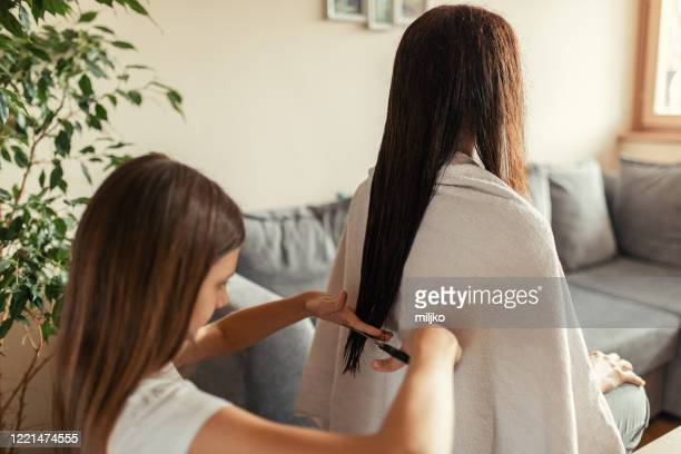 daughter doing haircut to her mother at home - miljko stock pictures, royalty-free photos & images