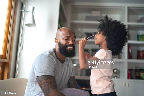daughter doing makeup to shy father at home - stereotypical homemaker stock pictures, royalty-free photos & images