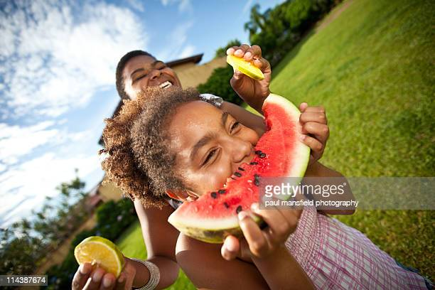 Daughter eats fruit with mother laughing