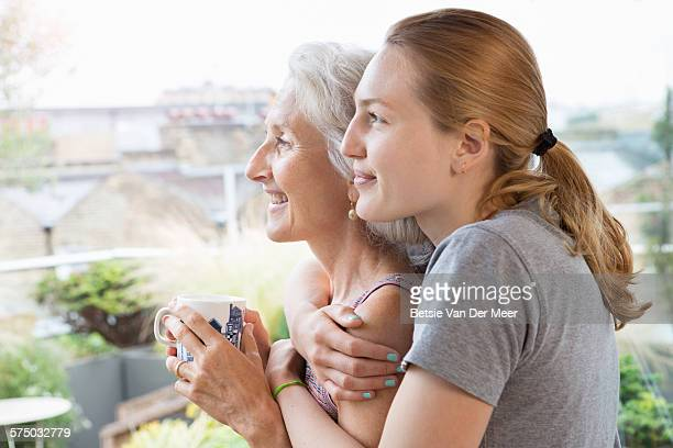 daughter embraces mother, looking out of window