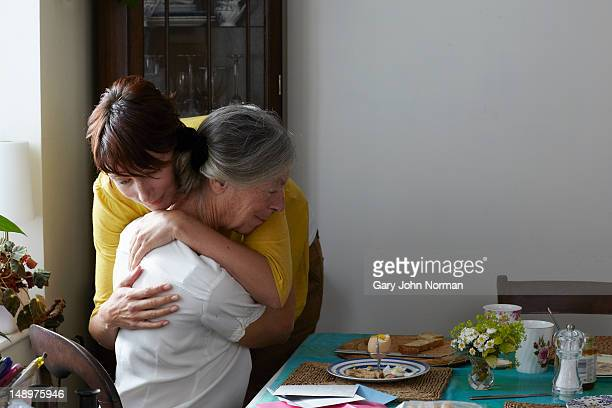 daughter embracing elderly mother in her home - care stock pictures, royalty-free photos & images